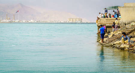 Dibba, Al Fujairah, UAE, November 25, 2016: local anglers fishing from the shore near Dibba Port, UAE