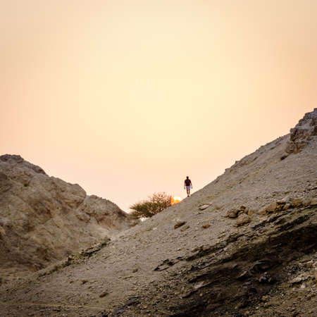 Hiker is watching sunset in Hajar Mountains of Ras Al Khaimah in UAE Stock Photo