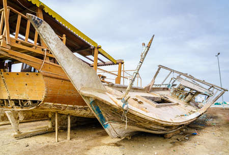 Old destroyed boats on shore near Dibba Port, UAE Stock Photo
