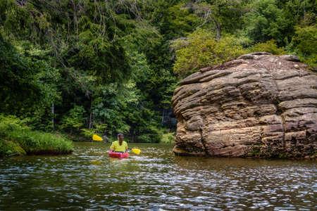 Woman is kayaking on Grayson Lake in Kentucky Stock Photo