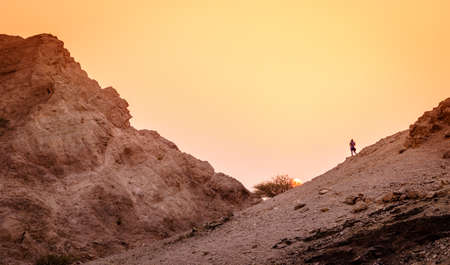 Hiker is watching sunset in Hajar Mountains of Ras Al Khaimah in UAE Stock Photo