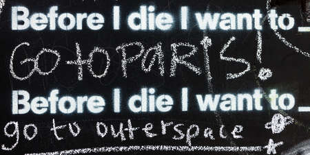 Fragment of a blackboard reading: Before I die I want to go to Paris