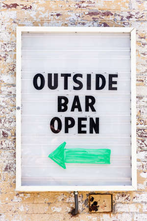 Sign on the wall reading: Outside Bar Open