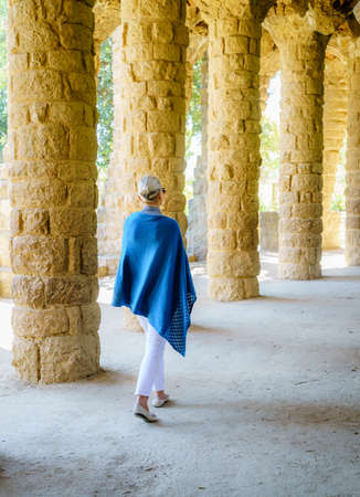 Woman walking through a colonnade in Park Guell in Barcelona