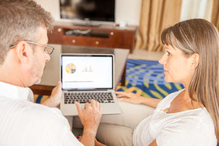 A man and a woman are working on a presentation on a laptop in the living room Stock Photo