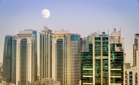 Full moon is rising over scyscrapers of Jumeirah Lake Towers distict of Dubai, UAE 版權商用圖片