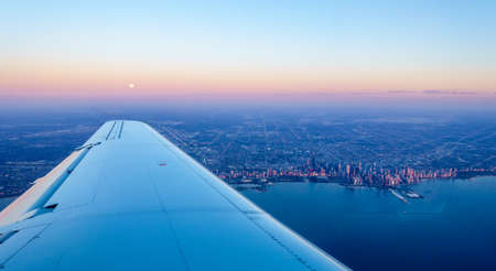 Scenic aerial view from a plane of full moon setting over Chicago