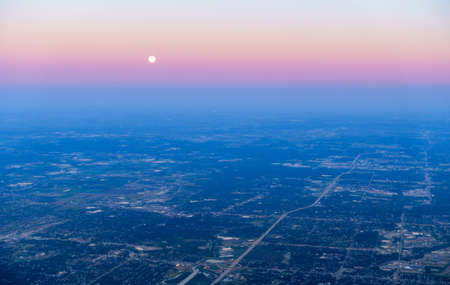 Scenic aerial view of fuul moon setting over Chicago, IL suburbs