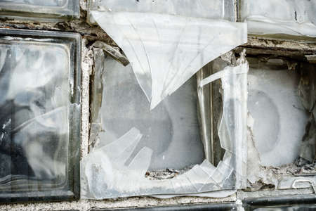 Close-up image of a broken glass box window in an abandoned building