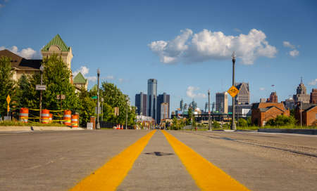 An empty street through an old Detroit city neighborhood with downtown buildings in the background Stok Fotoğraf