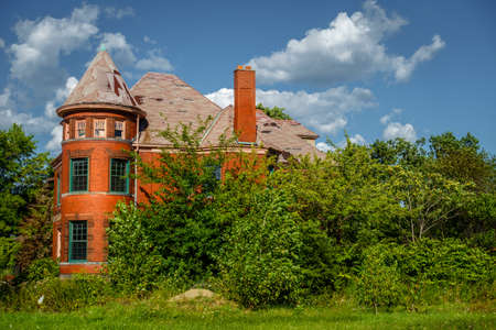 An abandoned house in the city of Detroit is taken over by plants and trees