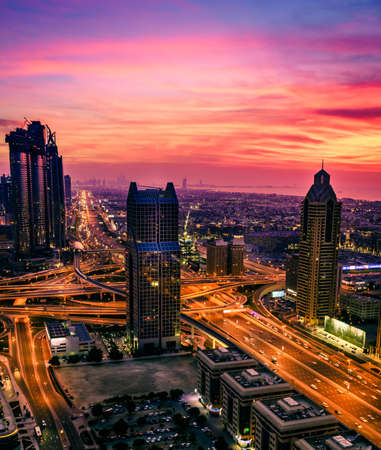 Birds eye view of Dubai downtown buildings and Sheikh Zayed Road after sunset