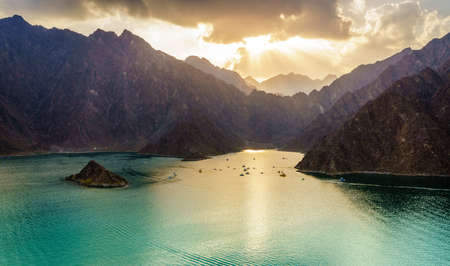 Scenic view of Hatta Lake and Hajar Mountains in the Emirate of Dubai, UAE at sunset