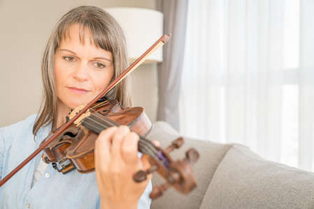 Mature woman playing violin in her urban apartment