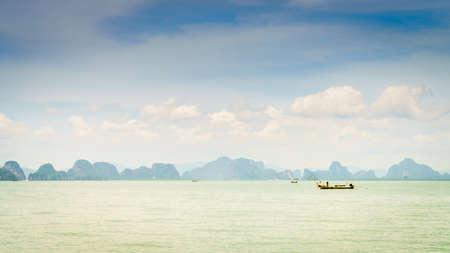 Small fishing boats in the Andaman Sea with Krabi coastline on the horizon Imagens