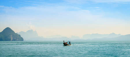Krabi, Thailand, November 7, 2017: Traditional Thai motor boat in the Andaman Sea with Krabi coastline in the backdrop Editorial