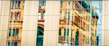 An old historic building reflected in windows of Kentucky International Convention Center in Louisville, KY Stock Photo