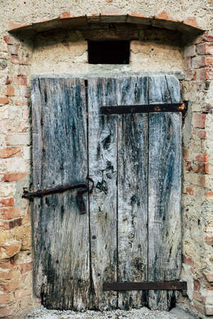 An old weathered door to wine cellar at a winery in Tuscany, Italy
