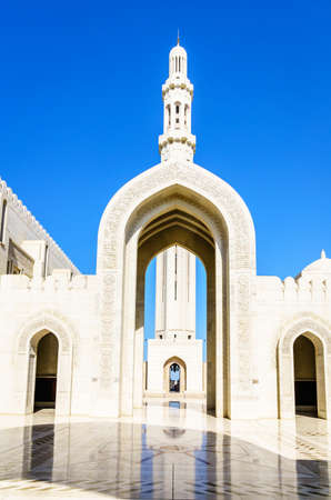 Main minaret and the entrance gate at the Sultan Qaboos Grand Mosque in Muscat, Oman