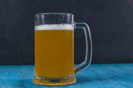 Mug of beer on wooden table on dark background