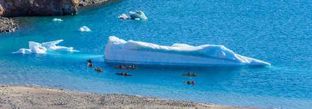 Kayaking in Arctic sea near iceberg Stock Photo