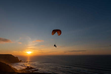Paraglider flying over thesea shore at sunset. Paragliding sport concept.