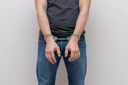 Adult prisoner male hands with handcuffs. Arrested man. Criminal concept.