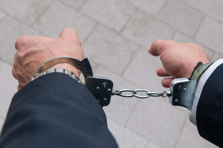 Arrested businessman or official in handcuffs. Corruption or economic crime concept.