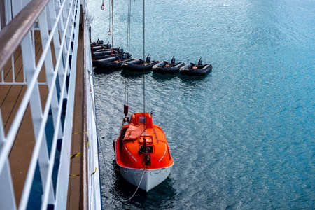 Lowering orange lifeboat to water in Arctic waters, Svalbard. Abandon ship drill. Lifeboat training. Man over board drill. Standard-Bild
