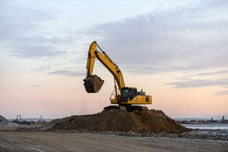 Yellow excavator working on construction site. The road construction. Stock Photo