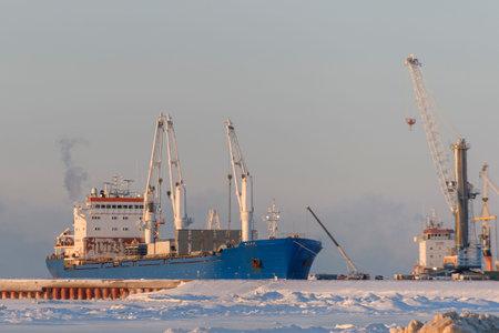Cargo vessel moored in arctic port. Winter time. Ice navigation. Loading in progress.