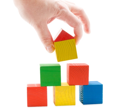 establishes: Hand establishes toy house on the wooden cubes pyramid. Isolated on white background.