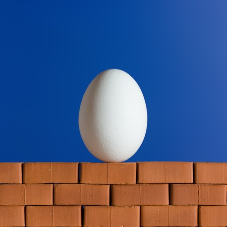 humpty dumpty: White egg on the red brick wall on the blue background Stock Photo