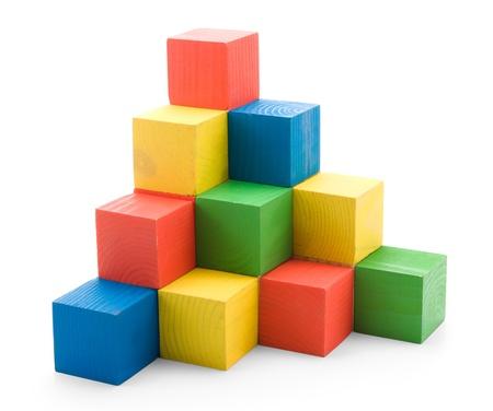 木製色の建物ピラミッドの白い背景で隔離のおもちゃをキューブします。