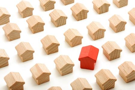 Uniek huis in groep houten huizen op een witte achtergrond Stockfoto
