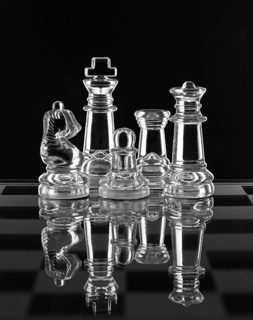 Glass chess family with reflection on black background Stock Photo