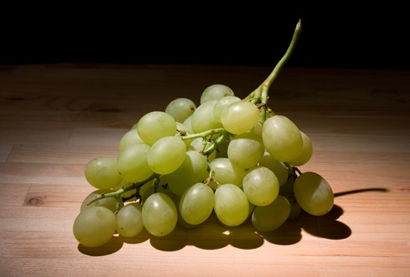 Green grapes bunch on a wooden table in the dark
