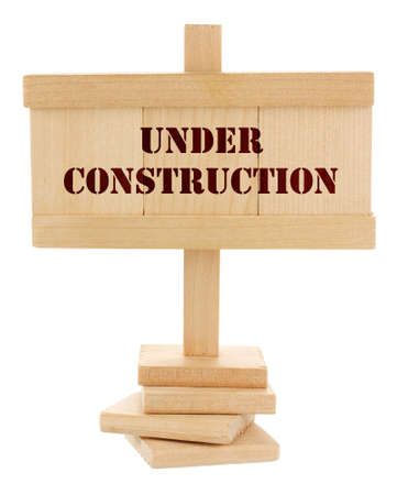 Under construction wooden tablet isolated on white photo