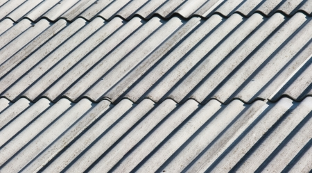 Old gray corrugated asbestos roof close-up view Stock Photo