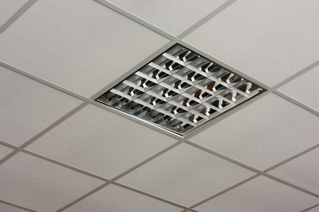Fluorescent office ceiling lamp built-in on the white ceiling close-up view