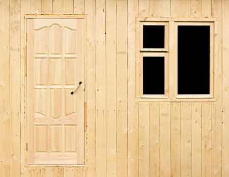 without window: Wooden wall of the rural house under construction made of the rough raw boards with the unfinished door and a window without platbands