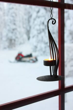 Decorative candle holder with burning candle hanging on window to the snowy winter yard with trees covered in snow and snowmobile photo