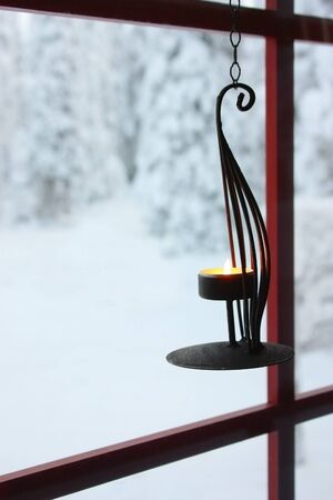 Decorative candle holder with burning candle hanging on window to the snowy winter yard with trees covered in snow photo