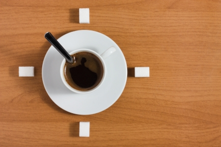 White coffee cup with saucer and sugar like a clock on a wooden brown table, top view