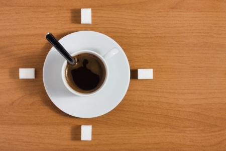 Witte kopje koffie met schotel en suiker als een klok op een houten bruine tafel, bovenaanzicht