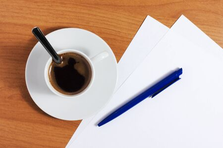 A cup of coffee on a wooden table with blank papers and blue pen, top view photo