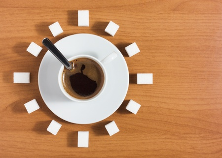 Cup of coffee with saucer and sugar like a clock on a wooden brown table, top view