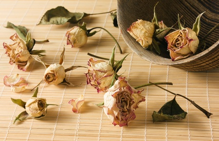 overturned overturn: Dried rosebuds scattered from overturned wooden bowl and lie on the reed mat close-up view