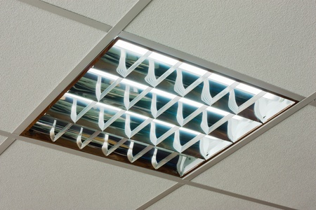 White office ceiling with built-in fluorescent shining lamp photo