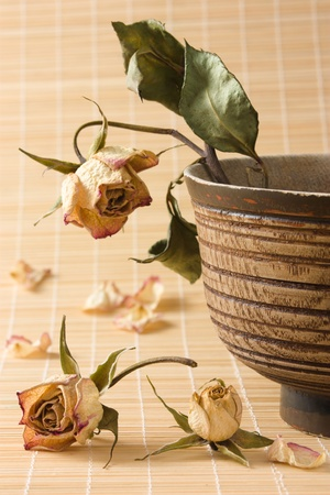 Dry rose with wilted green leaves in an old wooden bowl and dried rosebuds and petals on a straw mat photo